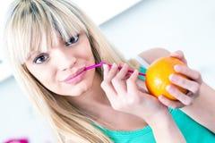 Fille belle buvant une orange d'une paille Photographie stock