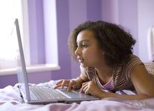 Fille Biracial sur l'ordinateur portatif image stock