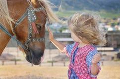 Fille blanche mignonne d'enfant en bas âge dans une robe rustique de style caressant le poney brun dans un domaine dans le jour e Images libres de droits