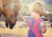 Fille blanche mignonne d'enfant en bas âge dans une robe rustique de style caressant le poney brun dans un domaine dans le jour e Photos libres de droits