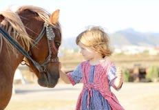 Fille blanche mignonne d'enfant en bas âge dans une robe rustique de style caressant le poney brun dans un domaine dans le jour e Photo libre de droits