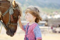 Fille blanche mignonne d'enfant en bas âge dans une robe rustique de style caressant le poney brun dans un domaine dans le jour e Image stock