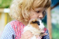 Fille blanche mignonne d'enfant en bas âge dans une robe rustique de style tenant un cobaye rouge sur ses mains Photo stock