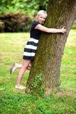 Fille blonde étreignant l'arbre Photographie stock libre de droits