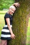 Fille blonde étreignant l'arbre Image libre de droits