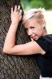 Fille blonde étreignant l'arbre Image stock