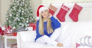 Fille blonde adorable s'asseyant sur le sofa dans le chapeau de Santa Claus banque de vidéos