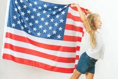 Fille blonde américaine tenant le drapeau national américain Photo libre de droits