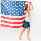 Fille blonde américaine tenant le drapeau national américain Photographie stock libre de droits