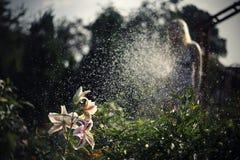 Fille blonde arrosant les fleurs image libre de droits