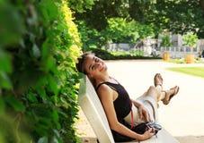 Fille blonde assez jeune songeuse s'asseyant sur un banc de parc à l'été ensoleillé dsy Image stock