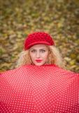 Fille blonde attirante avec le chapeau rouge regardant au-dessus de la pousse extérieure de parapluie rouge. Jeune femme attirante Photo stock