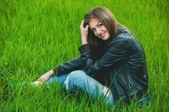 Fille blonde attirante et jeune dans un manteau gris et jeans se reposant sur l'herbe et le sourire photographie stock