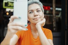 Fille blonde attirante faisant le selfie au café et buvant du café images stock