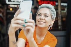 Fille blonde attirante faisant le selfie au café et buvant du café images libres de droits