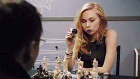 Fille blonde attirante jouant des échecs avec l'homme dans les verres et les promenades loin banque de vidéos
