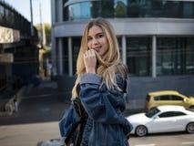 Fille blonde attirante souriant dans une veste de denim sur le fond d'un bâtiment moderne et d'un ciel bleu images stock