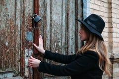 Fille blonde avec de longs cheveux, dans le manteau noir dans le chapeau, essayant d'ouvrir une porte verrouillée maison de briqu photo stock