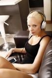 Fille blonde avec des écouteurs Photo libre de droits