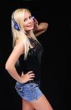 Fille blonde avec des écouteurs au-dessus de fond noir Photos libres de droits