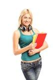 Fille blonde avec des écouteurs tenant des carnets Photos stock