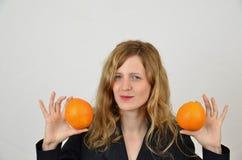 Fille blonde avec des oranges d'isolement sur le blanc Image libre de droits