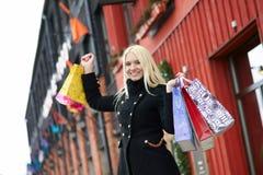 Fille blonde avec des paniers sur la rue Photos stock