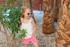 Fille blonde avec du charme dans des shorts roses et lunettes de soleil presque se tenant photo stock