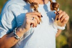 Fille blonde avec du charme tenant ses cheveux au coucher du soleil Photographie stock libre de droits