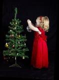 Fille blonde avec la robe rouge décorant l'arbre de Noël Images stock