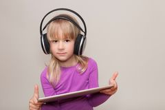 Fille blonde avec la Tablette et le casque Photos libres de droits