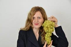 Fille blonde avec le groupe de raisins d'isolement sur le blanc Photos stock