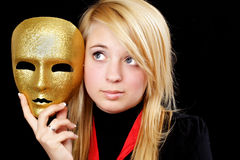 Fille blonde avec le masque d'or Photographie stock