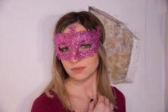 Fille blonde avec le masque de carnaval au-dessus du fond blanc mascarade photographie stock