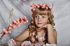 Fille blonde avec les fleurs blanches dans ses cheveux Photographie stock libre de droits