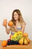 Fille blonde avec les fruits frais et le jus d'agrumes Photographie stock