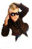 Fille blonde avec les lunettes de soleil noires sur le blanc images stock