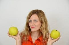 Fille blonde avec les pommes vertes d'isolement sur le blanc Photographie stock