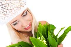 Fille blonde avec un bouquet des lis de la vallée Photos stock