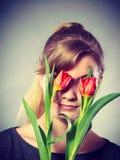 Fille blonde aveuglée par des fleurs Images libres de droits