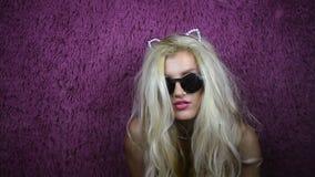 Fille blonde bizarre dans les lunettes de soleil et des oreilles de minou banque de vidéos