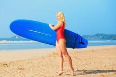 Fille blonde blanche de surfer dans le maillot de bain rouge tenant la planche de surf bleue photo libre de droits