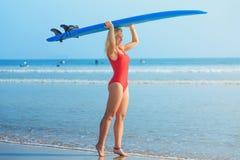 Fille blonde blanche de surfer dans le maillot de bain rouge tenant la planche de surf bleue sur la tête photographie stock libre de droits