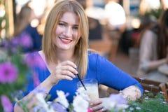 Fille blonde caucasienne de charme dans une robe bleue se reposant à une table dans seul un café de ville et l'attente photo stock