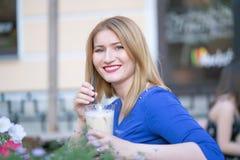 Fille blonde caucasienne de charme dans une robe bleue se reposant ? une table dans seul un caf? de ville et l'attente photos libres de droits