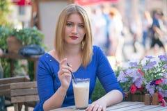 Fille blonde caucasienne de charme dans une robe bleue se reposant ? une table dans seul un caf? de ville et l'attente image stock