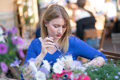 Fille blonde caucasienne de charme dans une robe bleue se reposant ? une table dans seul un caf? de ville et l'attente photographie stock