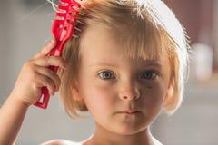 Fille blonde caucasienne de pensée sérieuse franche ou de jeune bébé triste avec le petit peigne d'éraflure avec la brosse de che Images stock