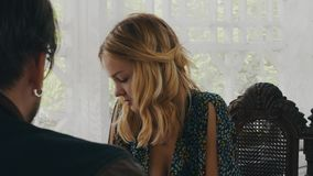 Fille blonde causant avec l'homme adulte à la table sur la terrasse de la maison de campagne Sucrerie banque de vidéos