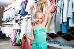 Fille blonde chez la boutique de vêtements des enfants Photo stock
